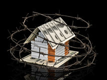 The cigarette house with a roof from dollars behind a barbed wir Stock Photo