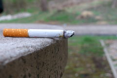 Cigarette. Left on the table. Big detail Stock Photos