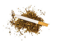 cigarette lies on a piece of dry tobacco Royalty Free Stock Photos