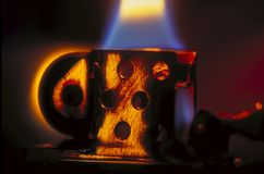 Cigarette lighter flame with amber highlights. A retro cigarette lighter burns with a blue flame, tapering to yellow. Amber light is reflected from the metal of Royalty Free Stock Photography