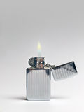 Cigarette Lighter - Lit. Retro chrome cigarette lighter - lit stock photo