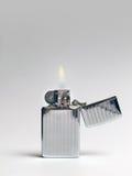 Cigarette Lighter - Lit. Retro chrome cigarette lighter - lit Stock Photo