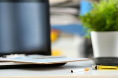 Cigarette and lighter lying at worktable Stock Image