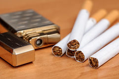 Cigarette and lighters placed on the wooden floor Royalty Free Stock Photos