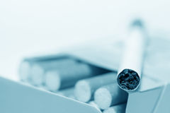 Cigarette lying on pack (blue toned) Stock Image
