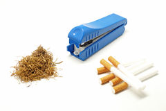 Cigarette making machine with cigarette tube and tobacco leaves Royalty Free Stock Image
