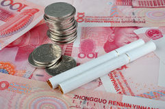 Cigarette and money, bill and coins. Cigarette and money, means expensive and harmful or lose money Royalty Free Stock Images