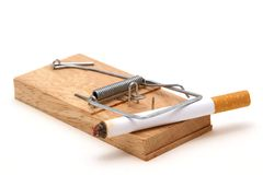 Cigarette in mousetrap. Macro view of burning cigarette in wooden mousetrap; white studio background stock images