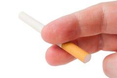 Cigarette non allumée dans sa main d'homme de doigts Photographie stock