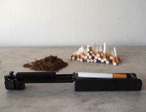 Cigarette rolling machine with empty cigarettes and tobacco on background stock photography