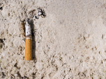 A cigarette in sand ashtray. Royalty Free Stock Image