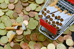 Cigarette in the shopping cart and money. Buying cigarettes lose money and health Royalty Free Stock Image