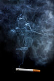 Cigarette and smoke. One lighted cigarette and the smoke it creates, over a black background Stock Images