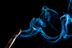 Cigarette smoke. Cigarette in front of black background. smoke goes up Royalty Free Stock Photo