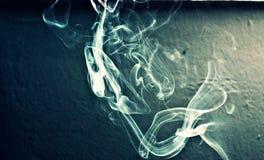 Cigarette smoke on blue background Stock Photo