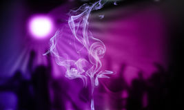 Cigarette smoke in a disco. Cigarette smoke with a party in the background Stock Photos