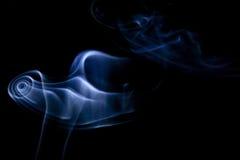 Cigarette smoke. Isolated blue cigarette smoke vortex on spot light on black background Royalty Free Stock Images