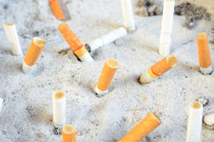 Cigarette stub in the sand Royalty Free Stock Images