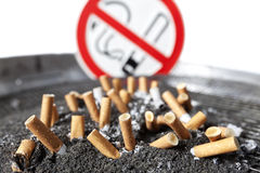 Cigarette stubs in ash with no smoking sign. Stock Photos