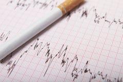 Cigarette sur l'impression d'ECG photographie stock