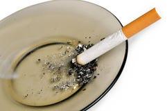 Cigarette sur le cendrier d'isolement Photographie stock