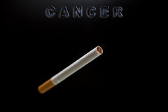 Cigarette, text cancer on black Stock Image