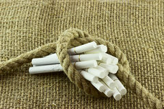 Cigarette tied with a rope Stock Image