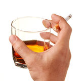 Cigarette and whisky...it's unhealthy. Hand with a cigarette and hold a glass of whisky Royalty Free Stock Photo