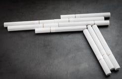 Cigaretten gillar ett vapen. arkivfoto