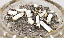 Cigaretter och aska i ett askfat Fotografering för Bildbyråer
