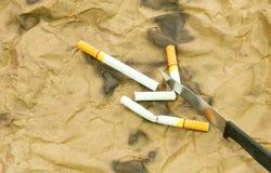 Cigaretter och knivar Arkivbild