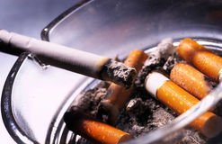 Cigarettes. Smoke and cigarettes in ash-tray Royalty Free Stock Photography