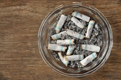 Cigarettes. Cigarette butts in a glass ashtray Royalty Free Stock Images