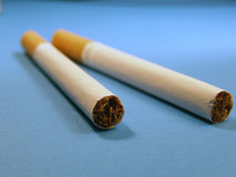 Cigarettes. Two cigarettes over blue Stock Photography