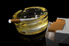 Cigarettes. And ashtray with one cigarette on black Stock Photo