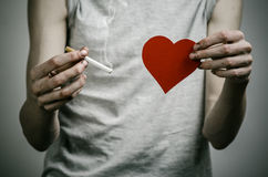 Cigarettes, addiction and public health topic: smoker holds the cigarette in his hand and a red heart on a dark background in the Stock Photos