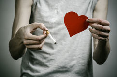 Cigarettes, addiction and public health topic: smoker holds the cigarette in his hand and a red heart on a dark background in the Royalty Free Stock Photography