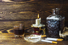 Cigarettes and alcohol candle Stock Image