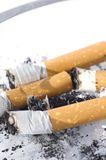 Cigarettes in ash tray. With small DOF royalty free stock photo