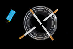 Cigarettes in an ashtray. Four cigarettes in an ashtray with blue lighter on a black background Stock Images