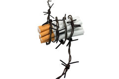 Cigarettes  in barbed wire. Cigarettes are wrapped in barbed wire Royalty Free Stock Photography
