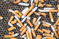 Cigarettes in a big iron ashtray Royalty Free Stock Photography