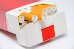 Cigarettes in box marked with skull and bones sign Stock Images