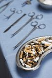 Cigarettes Butts And Operating Equipments On Table Royalty Free Stock Photos
