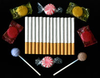 Cigarettes and Candy on Black Background Royalty Free Stock Photography