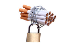 Cigarettes captured with chain and padlock Royalty Free Stock Photos