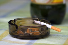Cigarettes. A cigarette is on an ashtray royalty free stock images