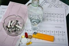 Cigarettes dans le cendrier, vodka sur la recherche médicale de table Photo stock