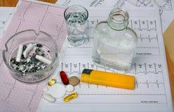 Cigarettes dans le cendrier, vodka sur la table Photographie stock libre de droits