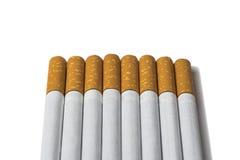 Cigarettes dans une rangée sur un blanc photos stock